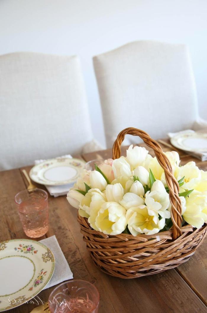 Korb gefüllt mit vielen gelben Tulpen, Tischdeko Frühling mit Naturmaterialien, gedeckter Tisch