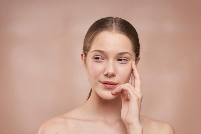 Ästhetische Dermatologie, Wallenstein Klinik, Derma Ästhetik, dunkelblonde Frau mit Hand auf dem Gesicht
