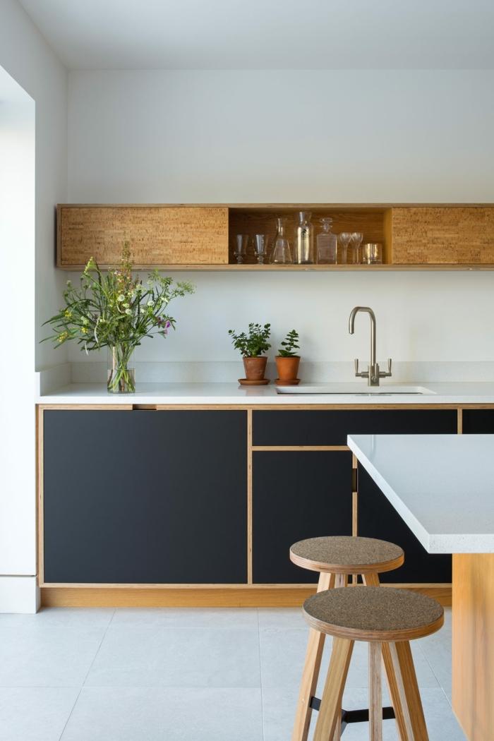 Küchenmöbel aus Holz in blaue Farbe, Kücheninsel mit weißer Arbeitsplatte, zwei kleine Stühle