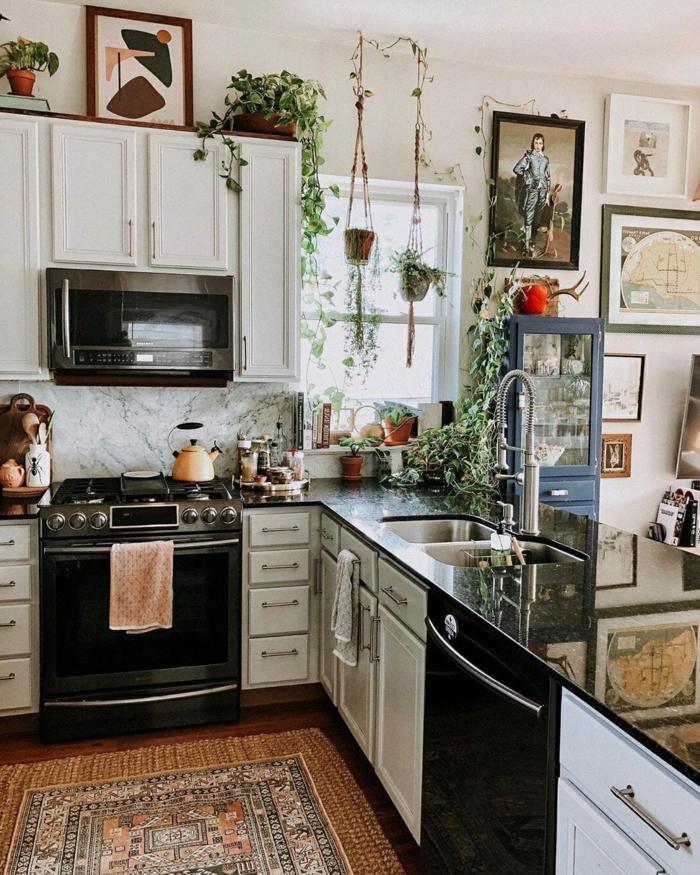 Innenarchitektur im bohemischen Stil mit vielen grünen Pflanzen, Ikea Küche Inspiration, viele aufgehängte Bilder an die Wand, schwarz und weiße Möbel
