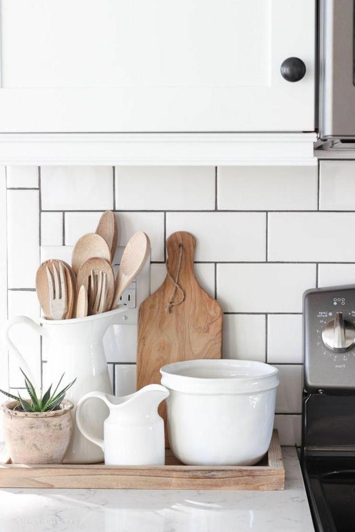 Deko Ideen Küche, Besteck und Schneidebrett aus Holz, moderne Innenarchitektur, kleine grüne Pflanze, große weiße Schale