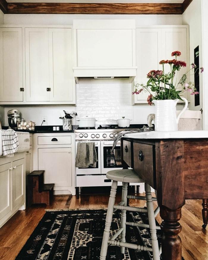 Innenarchitektur im bohemischen Stil, Küche modern weiss mit einem großen Holztisch, schwarzer Teppichm Vase mit lila Blumen