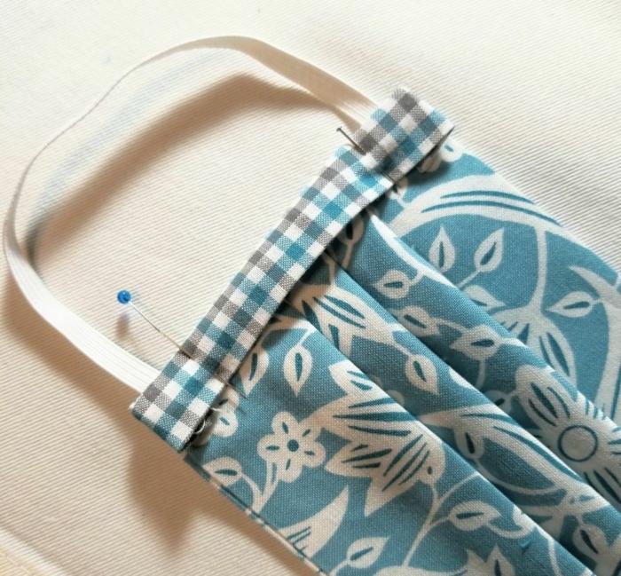 blaue Gesichtsmaske mit weißen Blumen, Atemschutzmaske Brillenträger, zwei Stecknadeln
