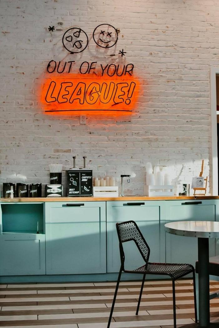 weiße Ziegelwand mit einem großen Neonlichtschild, Küchenschränke in blauer Farbe, schwarzer Stuhl, Küchen Dekorieren Tipps