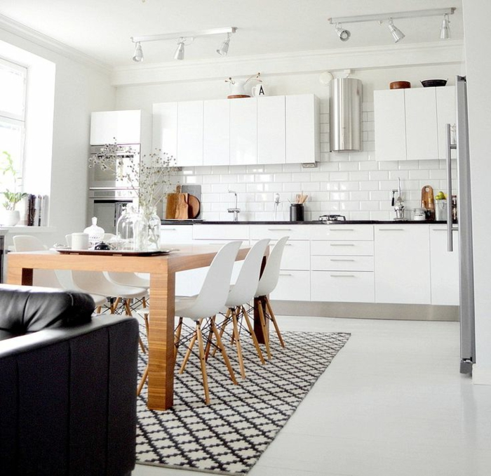 großer Esstisch aus Holz mit weißen Stühlen, schwarz weißer Teppich, monochrome weiße Küchenschränke, Couch aus Leder in schwarz, designer Küchen