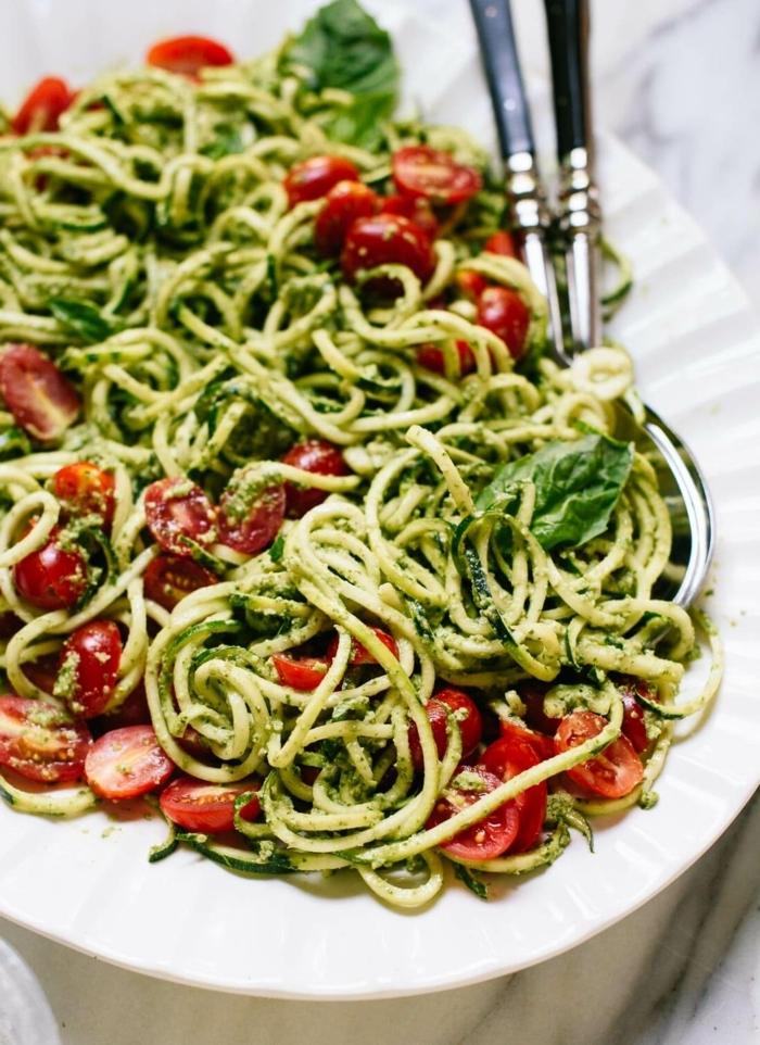 pasta mit zucchini und tomaten garniert mit pesto soße und frischem basilikum