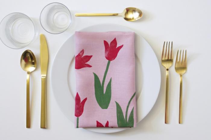 Pinke Serviette mit Abdruck von einer roten Tulpe auf einem weißen Teller, goldener Besteck, pinterest basteln