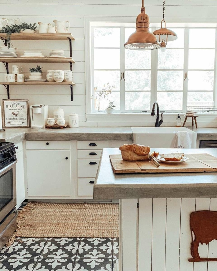 Küche u Form mit Fenster, offene Regale mit vielen Tassen und Tellern, monochrome Einrichtung in weiß, Lampen in Kupferfarbe