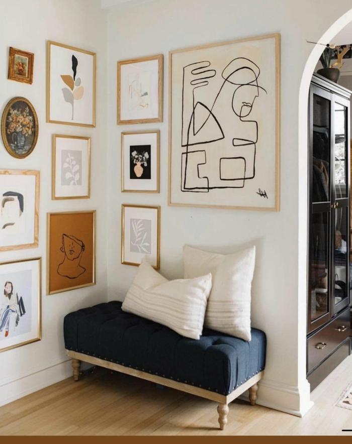 viele abstrakte Bilder, kleiner Hocker mit zwei weißen Kissen, Deko für die Wohnung Inspiration