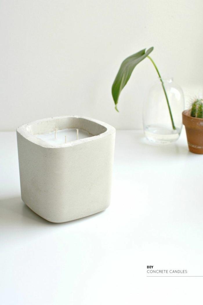 Kerzenhalter aus Beton mit einer kleinen Kerze, Betonarbeiten selber machen, grünes Blatt in einer Vase