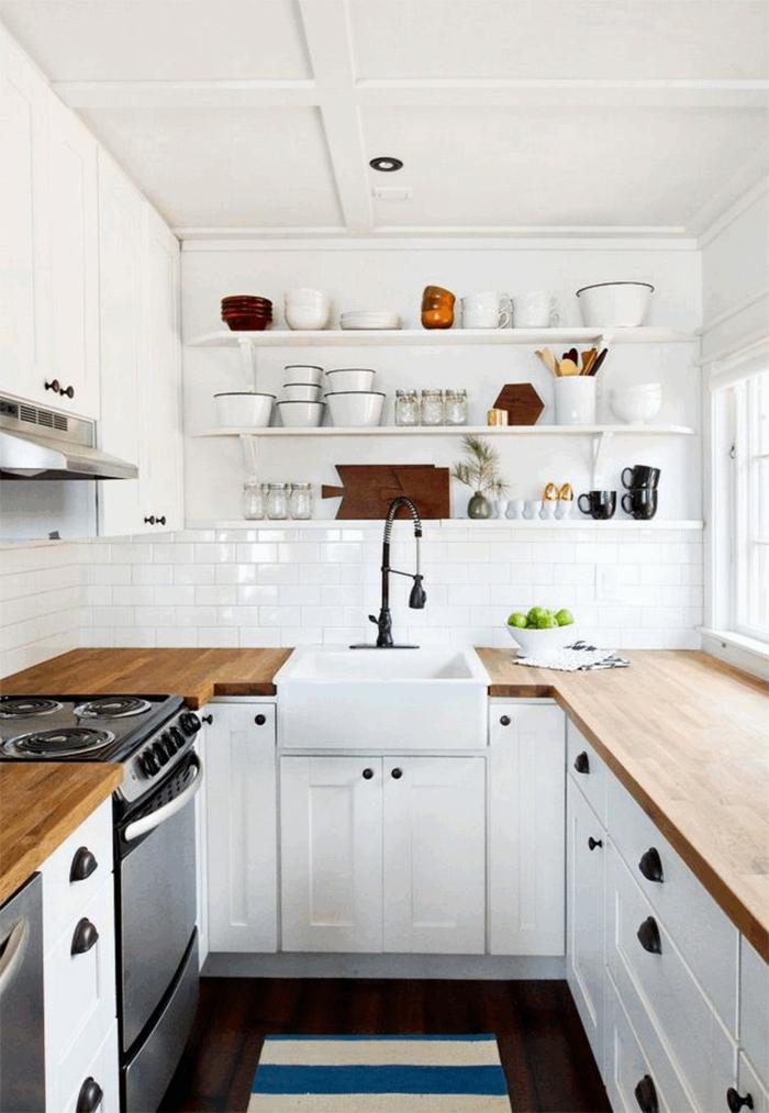 Kleine Küche u Form mit Fenster, weiß blauer Teppich, Arbeitsplatte aus Holz, Tassen und Teller auf einem Regal