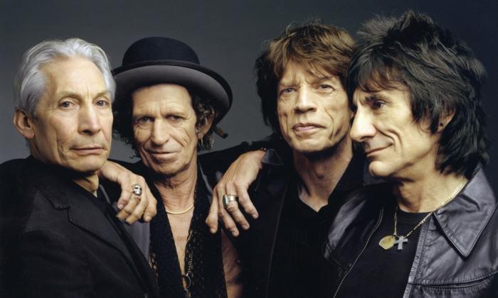 die vier mitglieder der band the rolling stones, ein mann mit halskette mit kreuz, living in a ghost town, mick jagger, mann mit schwarzem hut