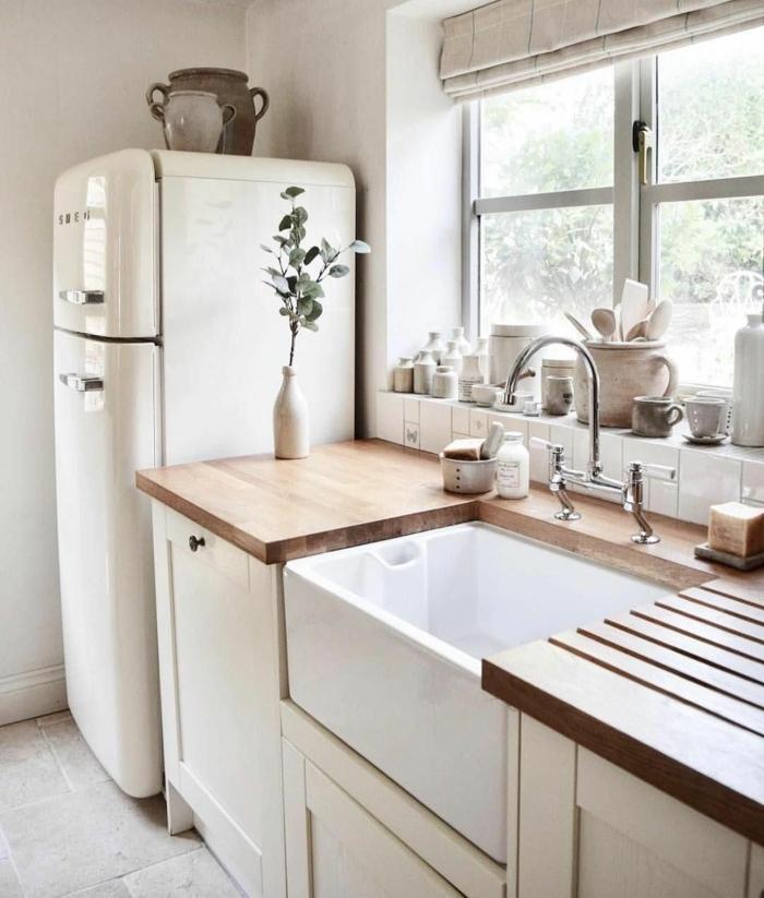 Monochrome Farbgestaltung in weiß mit Arbeitsplatte aus Holz, Küchen Innenausstattung mit Fenster, großer Kühlschrank