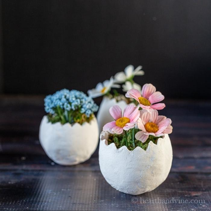 Drei kleine Pflanzer aus Ton mit blauen und pinken Blumen, frühlingsdeko basteln mit naturmaterialien