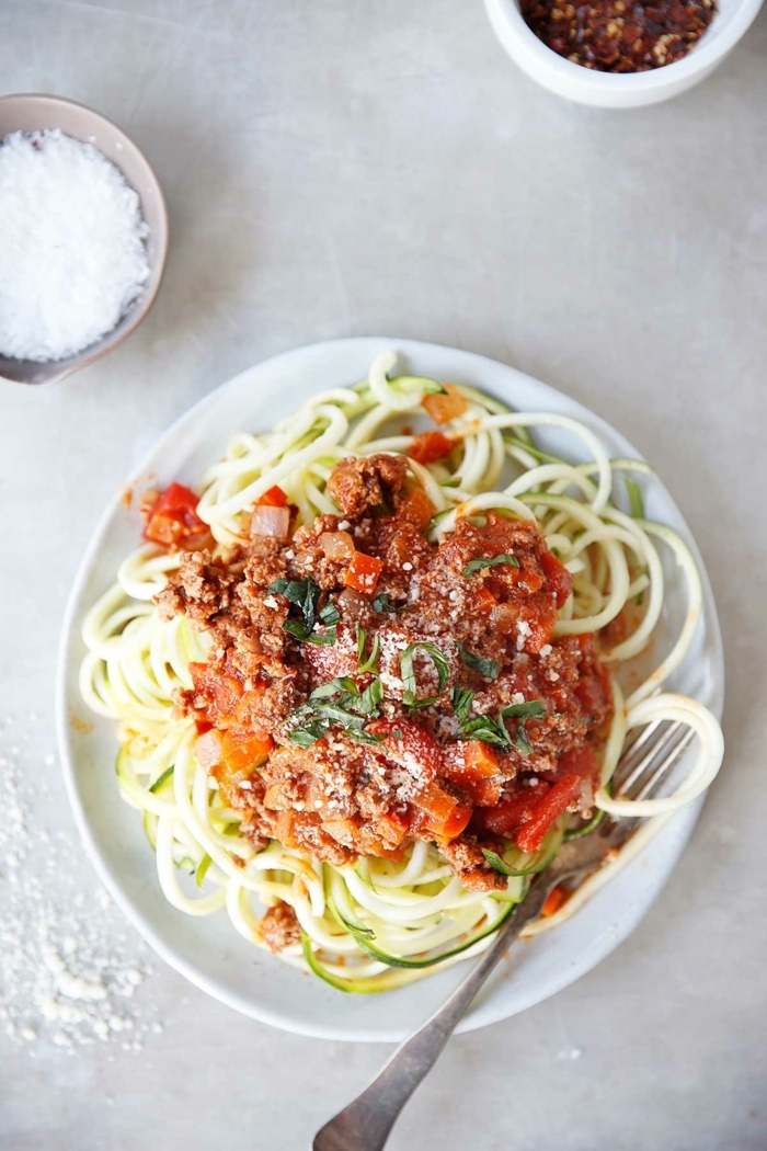 zucchini spaghetti bolognese garniert mit parmesan, paasta mit hachfleisch und tomatensoße