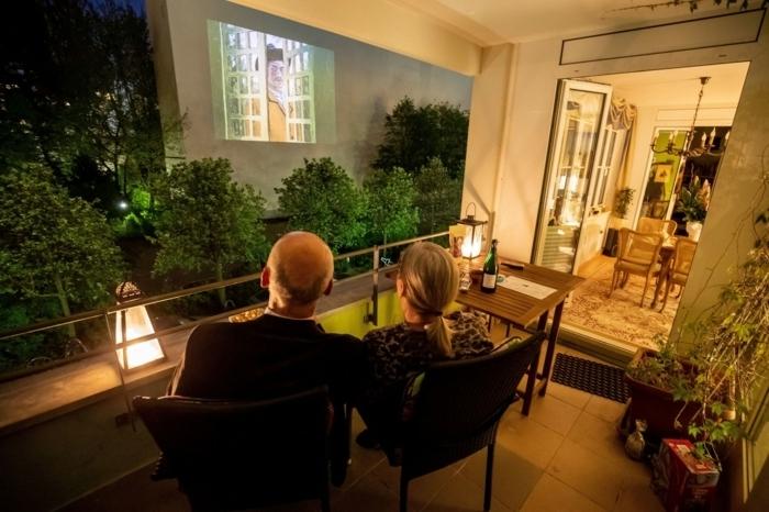 eine terrasse mit lampen und pflanzen, kino un berkiner hinterhöfe, ein gebäude mit einer fassadenwand als leinwand