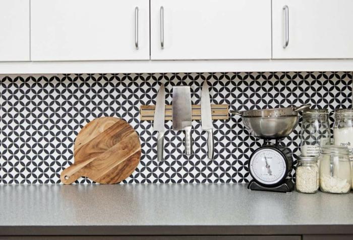 Wandgestaltung Küche mit schwarz weißer Tapete, Schneidebrett aus Holz, drei große Messer, weiße Küchenschränke