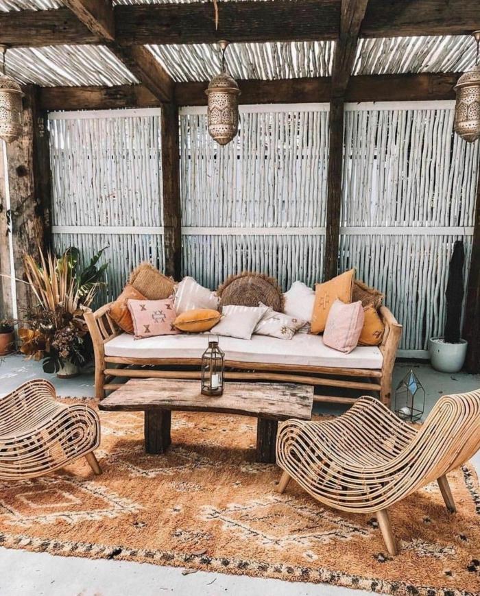 Boho Chic Einrichtung von einem Garten, Zaunideen mit Bambus in weiß, ockerfarbener Teppich, Sofa mit vielen Kissen