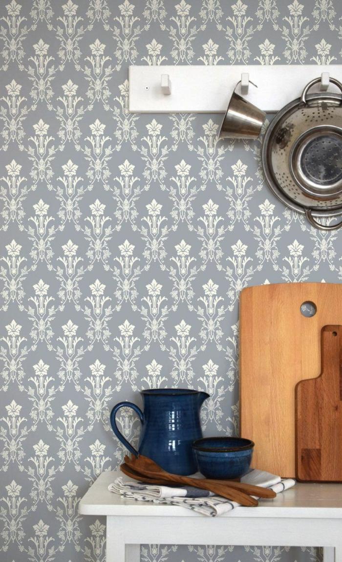 Interior Design im skandinavischen Stil, blaue Tapete Küche Landhaus, mit Blumenmotiven, blauer Keramikbecher und Keramikkanne, Schneidebrett aus Holz