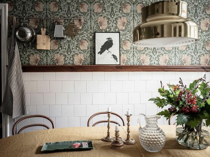 weiße Fliesen, Küchen Tapeten grün mit Blumenmotiven, Bild von einer schwarzen Rabe, Blumen in Vase, aufgehängte Küchenutensilien