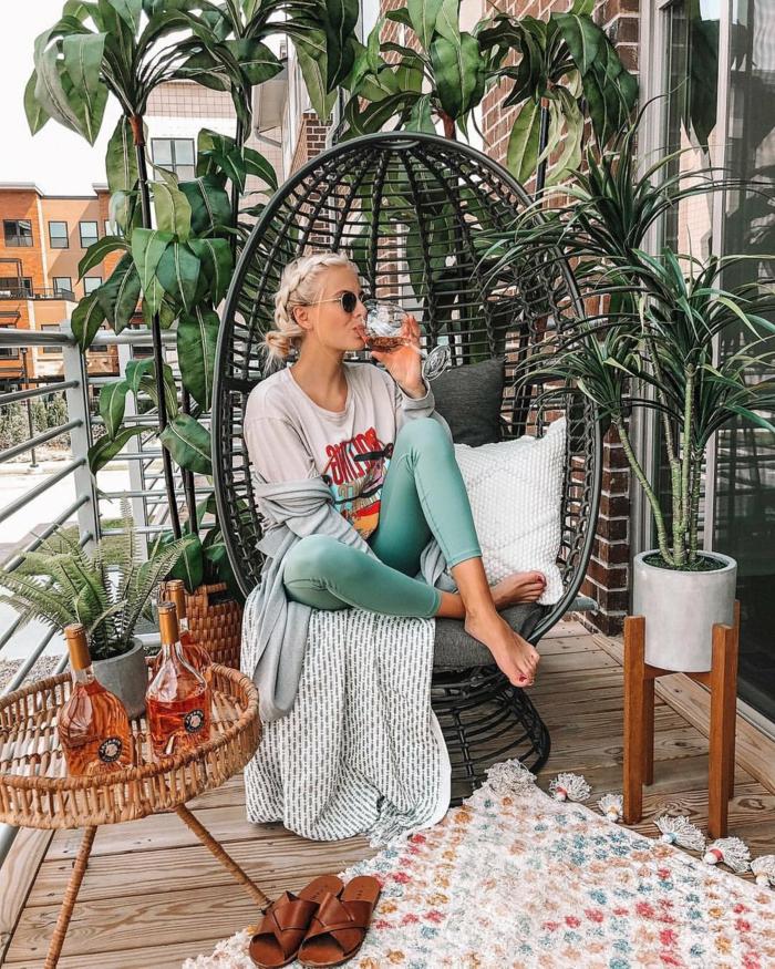 Terrassengestaltung mit Sichtschutz von großen Pflanzen, junge Frau sitzt in einer schwarzen Schaukel,