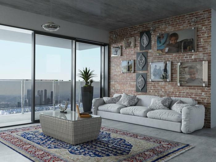 bunter Teppich Wohnzimmer, großes weißes Sofa und Fenster, Backsteinwand mit aufgehängten Bildern