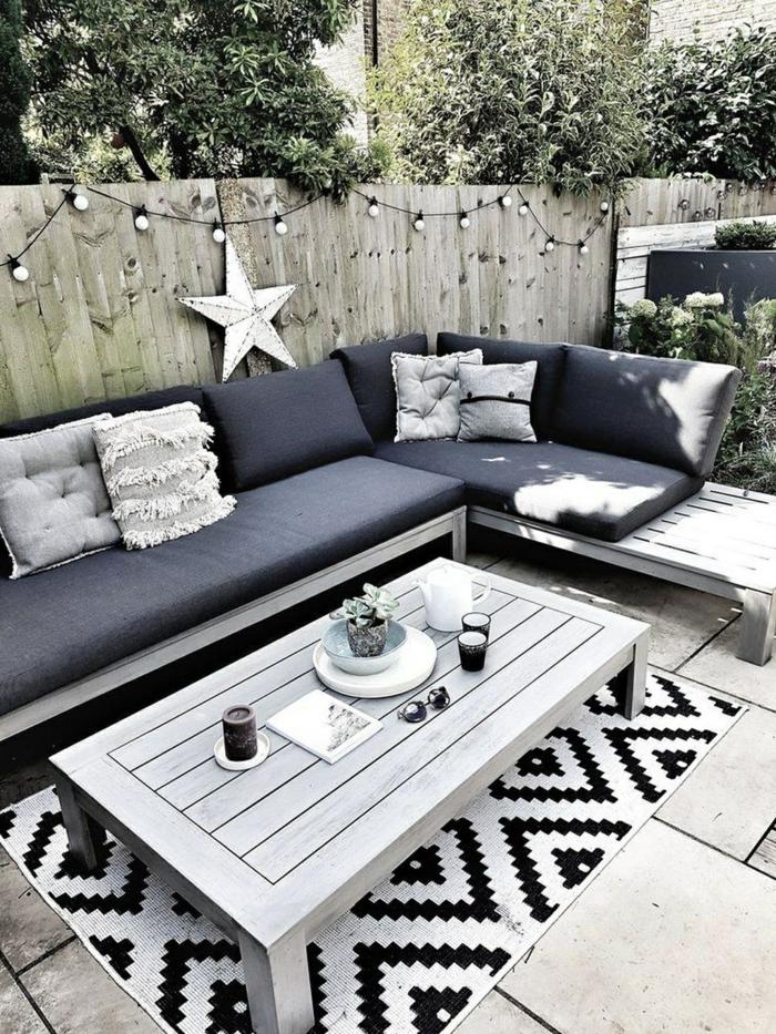 Sichtschutz Terrasse Holz, Gartenzaun mit aufgehängten Leuchten, Ecksofa mit blauer Polsterung, schwarz weißer Teppich