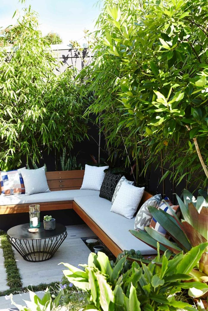 Sichtschutz Garten Ideen Selber machen mit großen Pflanzen, Ecksofa mit weißer Polsterung und schwarzen Kissen
