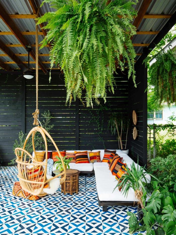 Boden mit blau weißen Fliesen, hängende grüne Pflanze, Ecksofa mit weißer Polsterung und bunten Kissen, Sichtschutz Garten, Zaunideen in schwarz
