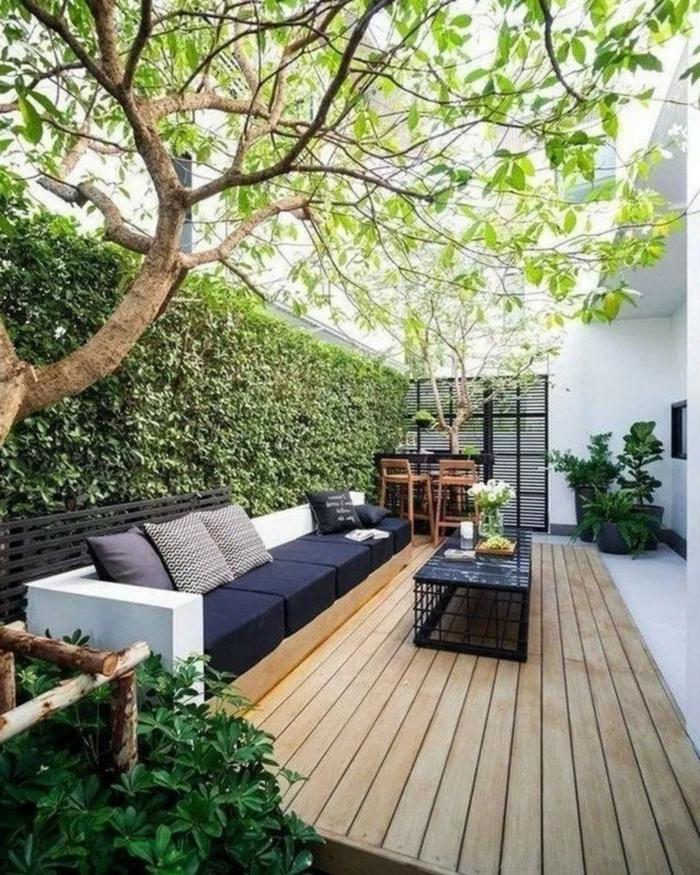 Gartengestaltung Sichtschutz Beispiele mit Pflanzen, minimalistische Einrichtung von Terrasse mit schwarzem Sofa, Boden aus Holz,
