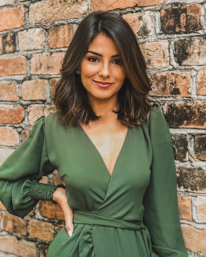 Frisuren 2020 Frauen mittellang, Dame im grünen Jumpsuit, braune Haare, Foto vor einer Backsteinmauer