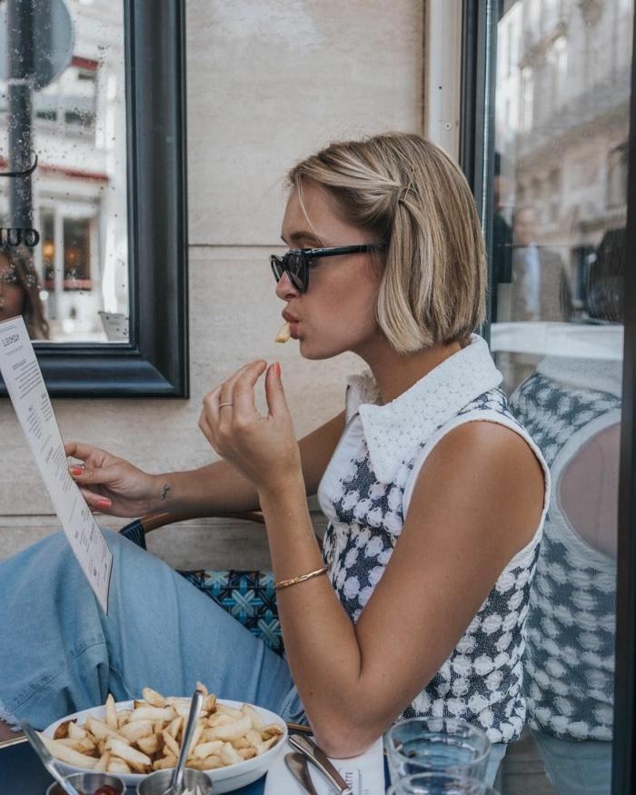 Damen Frisuren halblang, junge Frau isst Pommes im Restaurant, elegantes Outfit in Jeans und weiß-blaue Bluse, Bob Frisuren 2020