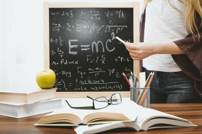 schwarze Tafel mit Gleichungen, viele Bücher auf dem Tisch, Weiterbildung nach Ausbildung, grüner Apfel, schwarze Brillen