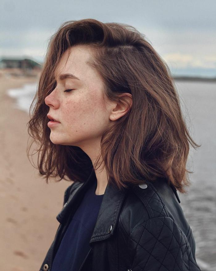 junge Dame mit schwarzer Lederjacke und blauer T-Shirt, braune Haare, Bob Frisuren kurz stufig