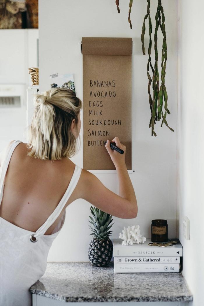 Frau im weißen Kleid, schreibt auf einem Stück Papier, blondes Haar, Bob Frisuren 2020 mittellang