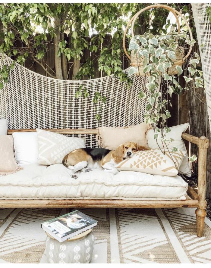 Hund liegt auf einem Sofa aus Bambus mit weißer Polsterung, Garten Trennwand Holz, Sichtschutz mit Zaun und Baum