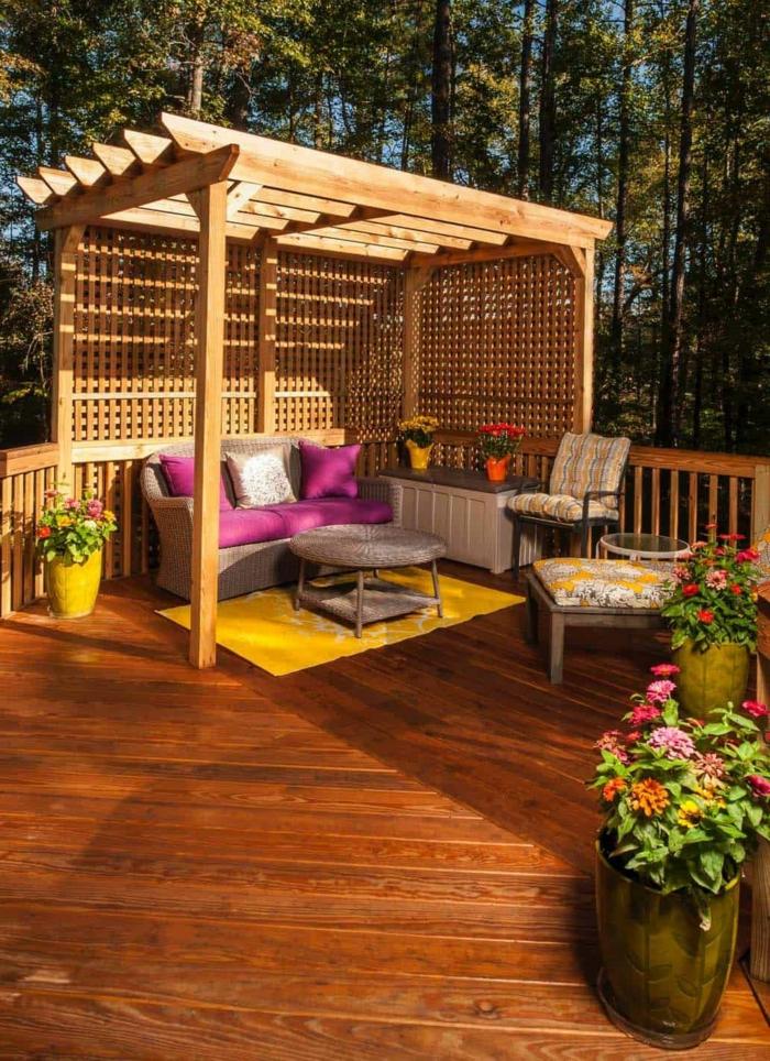 Terrassengestaltung mit Sichtschutz, große Gartenlaube aus Holz mit Sofa und Stühle, Dekoration mit Blumen