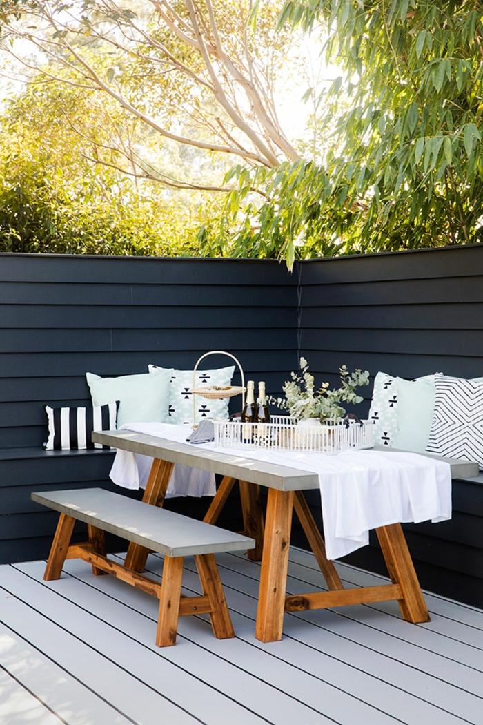 Gartenzaun Ideen Gestaltung in dunkelblauer Farbe, gedeckter Picknicktisch mit Bank