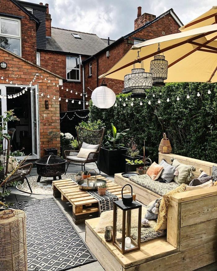 gemütliche und moderne Hinterhofgestaltung mit Grill, Sichtschutz Garten Pflanzen, Ecksofa und Tisch aus upcyclten Kisten