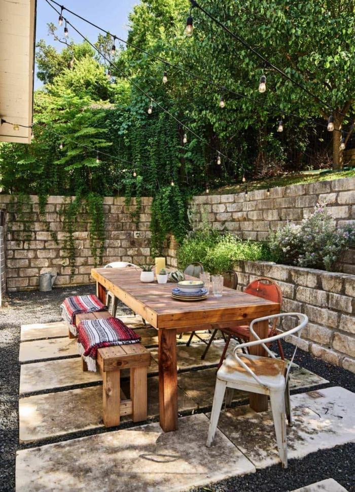 Gartenzaun aus Steinen, grüne Pflanzen und Bäume, großer Holztisch, Sichtschutz für Terrasse