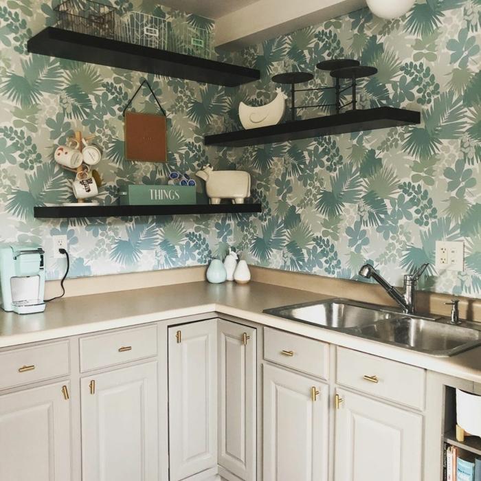 drei schwarze offene Regale, weiße Küchenschränke, grüne Küchen Tapeten mit floralem Muster