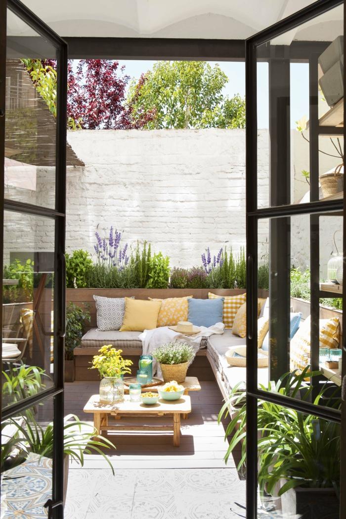 Sichtschutz Terrasse modern, großer weißer Gartenzaun, Ecksofa mit gelben und blauen Kissen, Dekoration mit vielen Pflanzen