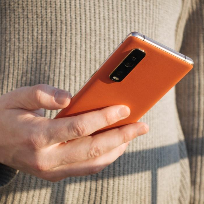 ein oranges handy des chinesischen hertsllers oppo mit vier kameralinsen, eine frau mit handy