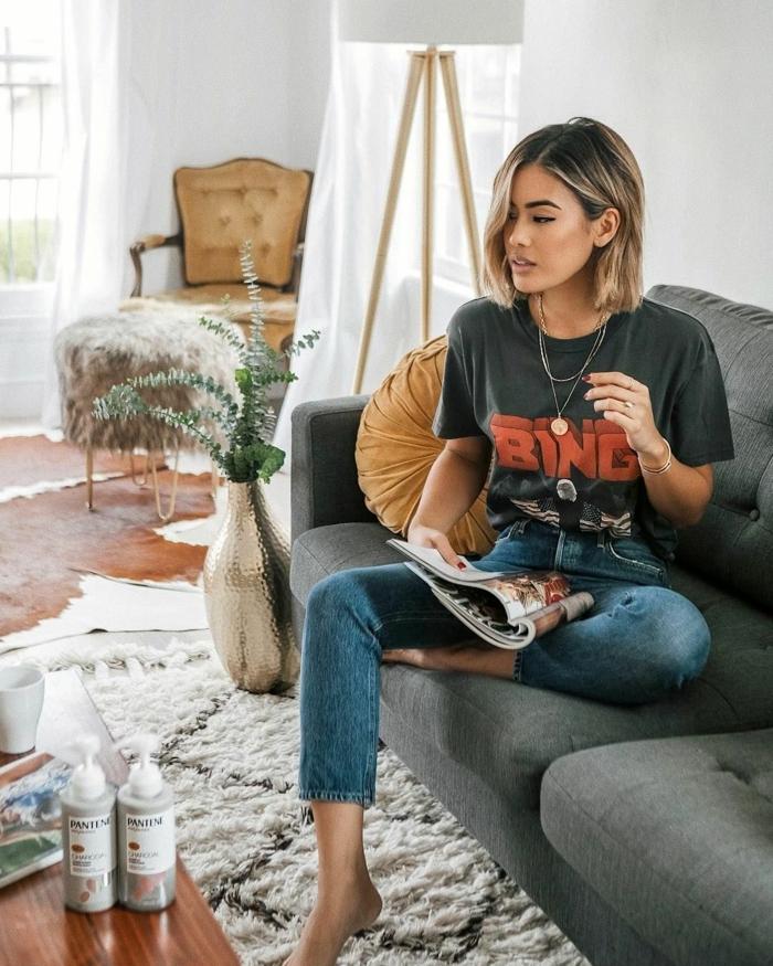 legere angezogene Dame in Jeans und schwarzes T-Shirt mit Print, Frisuren Frauen Mittellang, Bob Frisuren 2020, grauer Sessel