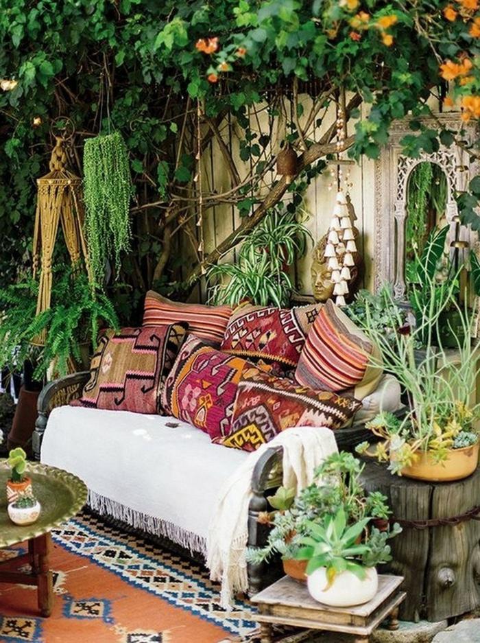 Bohemische Außeneinrichtung für den Garten, kleiner Sofa mit vielen bunten Kissen, Sichtschutz Terrasse modern, Gartenzaun und grüne Pflanzen