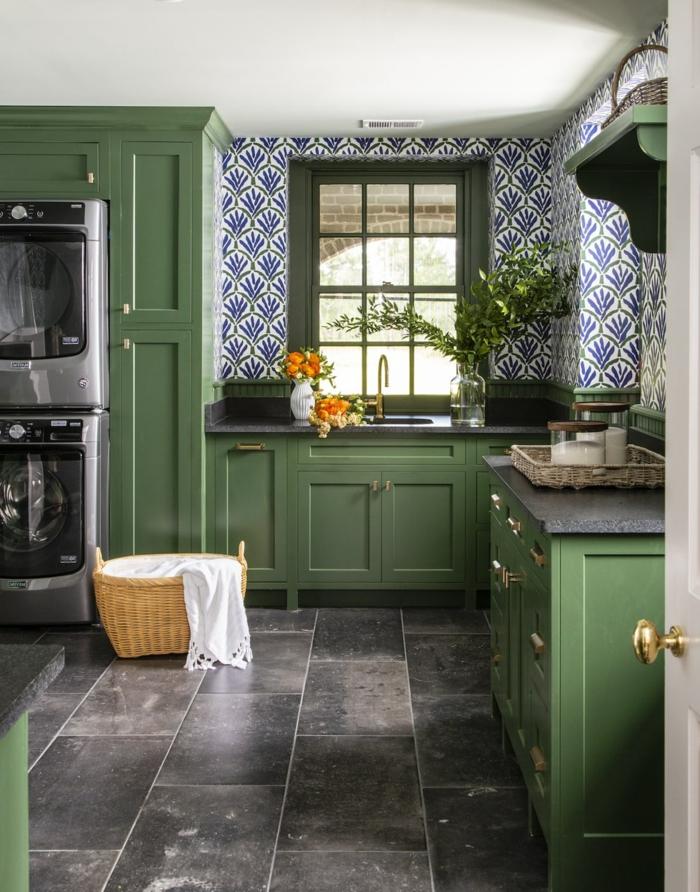 elegante Möbel in grüner Farbe, schwarze Waschmaschine und Trockner, Küchenwände gestalten mit blauen Tapeten