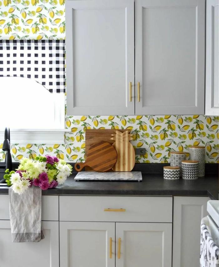 weiße Schränke mit schwarzer Theke, Tapeten für Küche mit Zitronen, Blumenstrauß mit weißen und lila Blumen