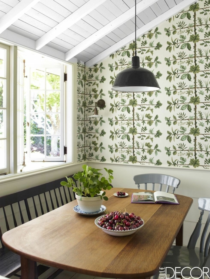 Wandgestaltung Küche mit Dachschräge und großem Fenster, moderner Tisch aus Holz, schwarze Lampe, Teller mit Kirschen