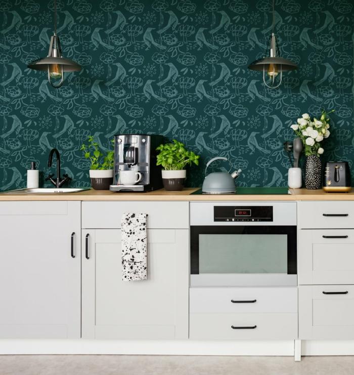 grüne Wand mit Lampen, elegante Küche mit weißen Möbeln, Pflanzen und Kaffeemaschine, Küchentapeten Inspiration