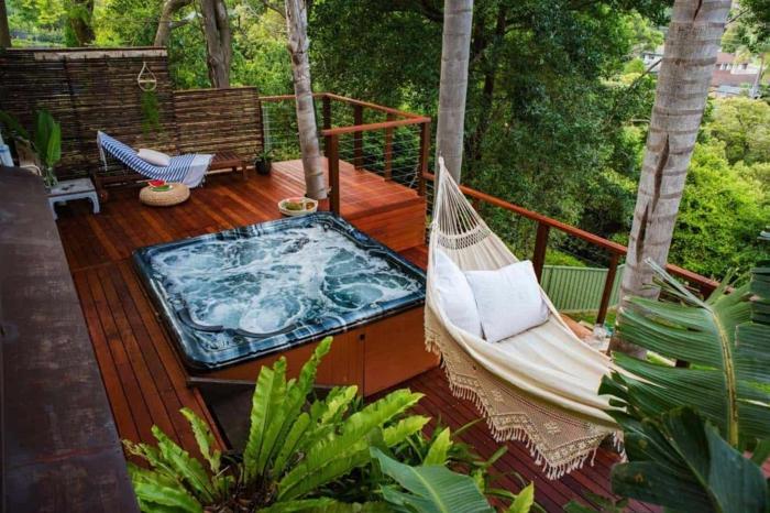Jacuzzi auf der Terrasse, Terrassengestaltung mit Sichtschutz, weiße Hängematte, moderne und luxuriöse Außeneinrichtung